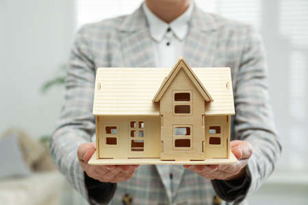 Real estate agent holding wooden house model indoors, closeup