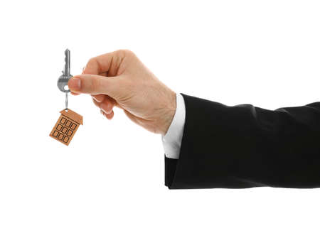 Real estate agent holding house key with trinket on white background, closeup Stok Fotoğraf - 135615084