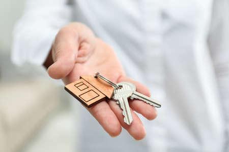 Agent immobilier tenant des clés de maison avec bibelot, gros plan