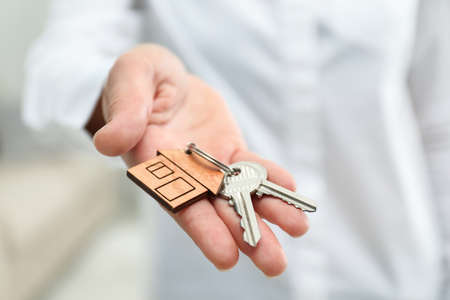 Real estate agent holding house keys with trinket, closeup