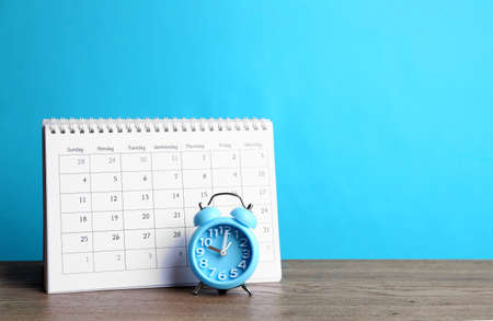 Calendar and alarm clock on wooden table against light blue background. Space for text Imagens