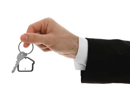 Real estate agent holding house key with trinket on white background, closeup