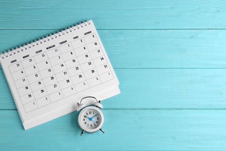 Calendar and alarm clock on light blue wooden background, flat lay. Space for text