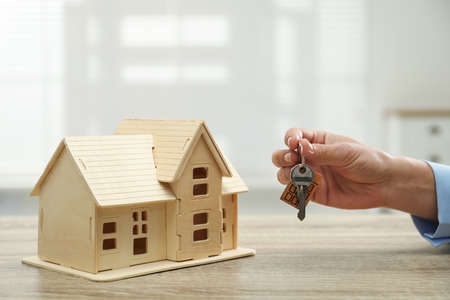 Real estate agent with house model and key at wooden table, closeup