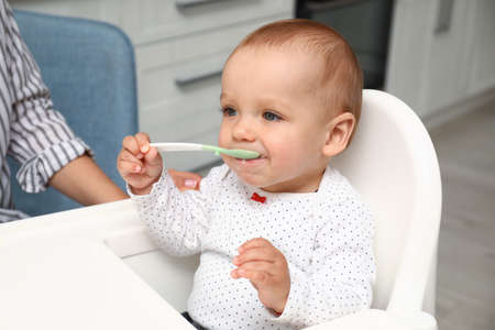 Cute little baby with spoon in highchair at home