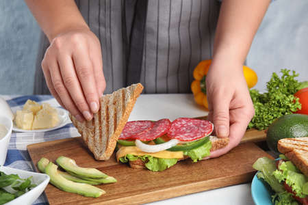 Woman making tasty sandwich with sausage at white  table, closeup 写真素材