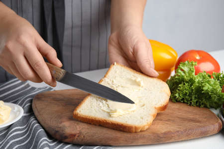 Woman spreading butter on sandwich at white table, closeup