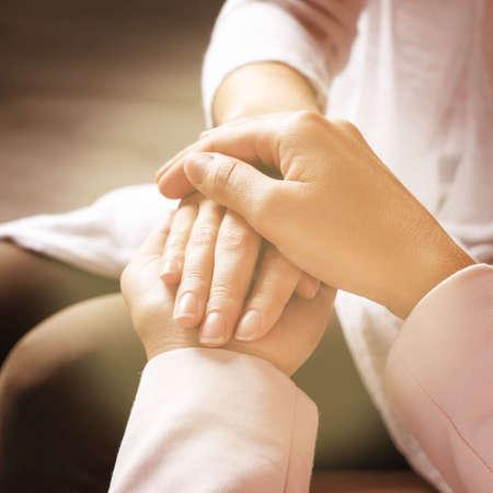Volunteer holding hands with woman in sunlit room, closeup