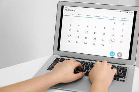 Woman using digital calendar on laptop in office, closeup