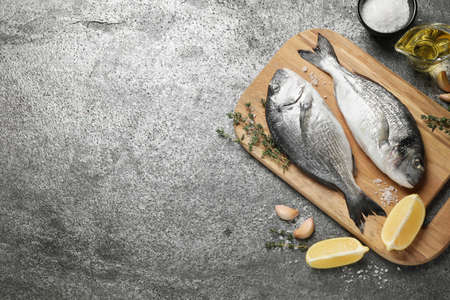 Flat lay composition with raw dorada fish on grey table, space for text Zdjęcie Seryjne