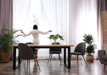 Woman near window in room decorated with plants. Home design ideas 版權商用圖片