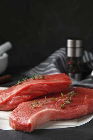 Fresh raw beef cut with thyme on black table