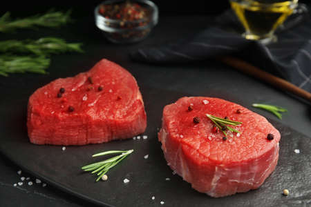 Fresh raw beef cut with spices on black table, closeup