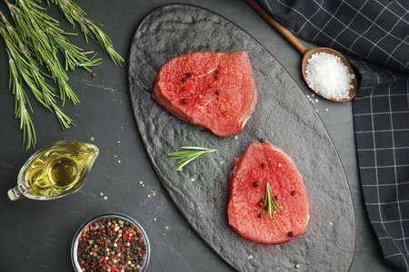Flat lay composition with fresh beef cut on black table Stock fotó