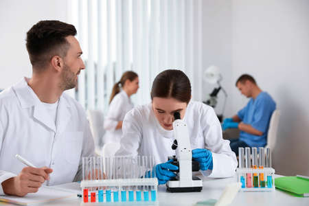 Medical students with microscope in modern laboratory