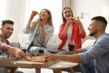 Group of friends eating tasty pizza at home