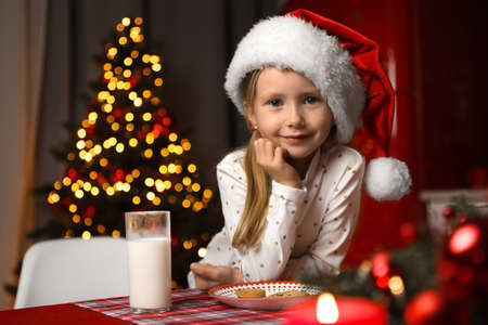 Cute little child with milk and cookies at table in dining room. Christmas time