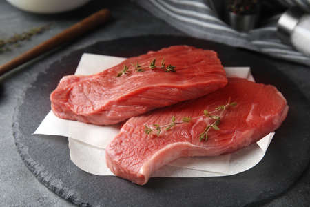 Fresh raw beef cut with thyme on grey table, closeup Stock fotó