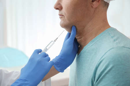 Mature man with double chin receiving injection in clinic, closeup