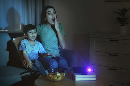 Emotional young woman and her son watching movie using video projector at home. Space for text