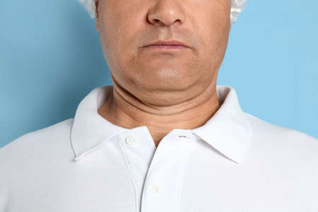 Mature man with double chin on blue background, closeup