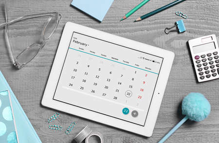 Flat lay composition of tablet with calendar app on grey wooden table Foto de archivo