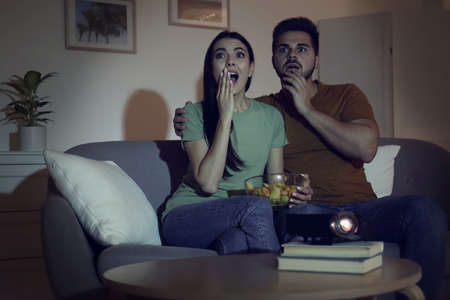 Emotional young couple watching movie using video projector at home