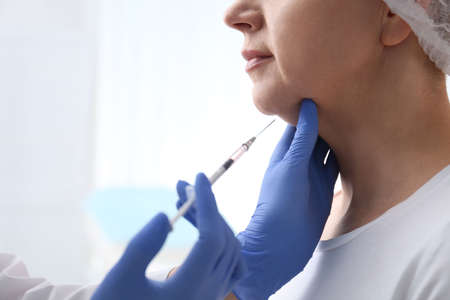 Mature woman with double chin receiving injection in clinic, closeup