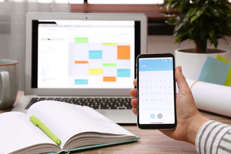 Frau mit Smartphone mit Kalender-App am Tisch, Nahaufnahme