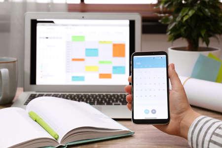 Vrouw met smartphone met kalender-app aan tafel, close-up