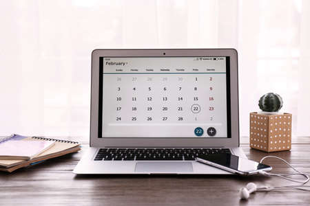 Laptop with calendar on wooden table at workplace