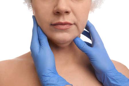 Médico examina a mujer madura sobre fondo blanco, primer plano. Cirugía de papada Foto de archivo