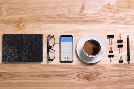 Flat lay composition of smartphone with calendar app on wooden table