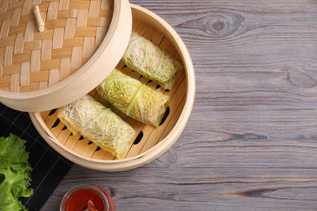 Delicious cabbage rolls in bamboo steamer on wooden table, flat lay. Space for text