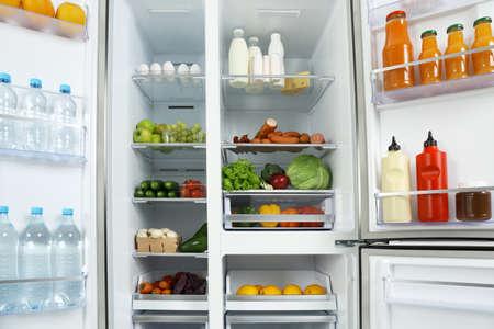 Refrigerador abierto lleno de diferentes productos frescos.