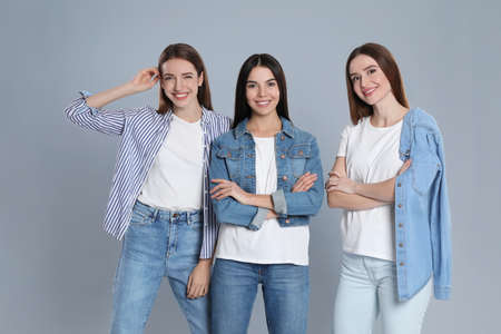 Group of young women in stylish jeans on grey background Banque d'images - 135497805