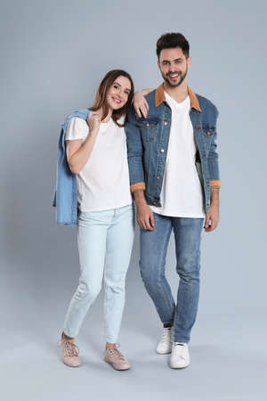 Young couple in stylish jeans on grey background Banque d'images - 135497946