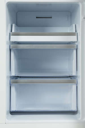 Shelves of empty modern refrigerator, closeup view