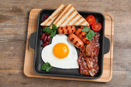 Delicious breakfast with heart shaped fried egg and sausages on wooden table, top view