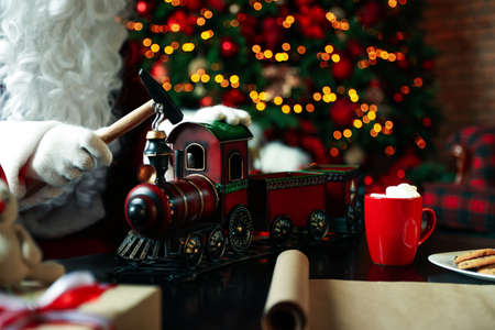 Santa Claus making new toy for Christmas in workshop, closeup