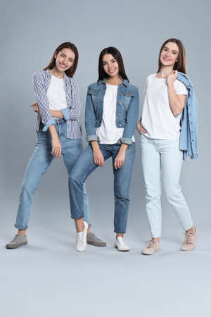 Group of young women in stylish jeans on grey background Banque d'images - 135497949