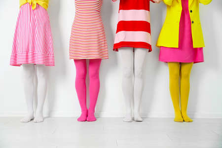 Women wearing colorful tights near white wall, closeup 스톡 콘텐츠