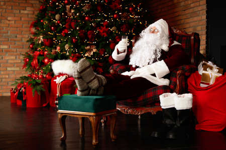 Santa Claus with glass of milk resting in armchair near Christmas tree Stock Photo
