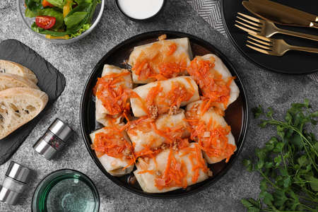 Delicious cabbage rolls served on grey table, flat lay