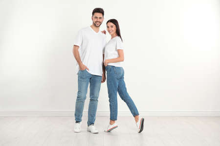 Young couple in stylish jeans near white wall Banque d'images - 135497950