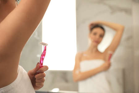 Young woman shaving armpit in bathroom, closeup