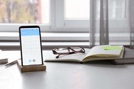 Modern smartphone with calendar on screen in office