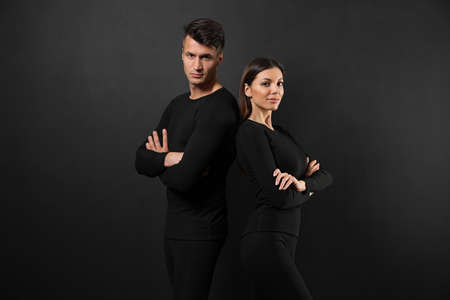Couple wearing thermal underwear on black background
