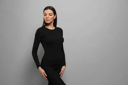 Woman wearing thermal underwear on grey background. Space for text