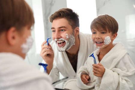 Dad shaving and son imitating him in bathroom